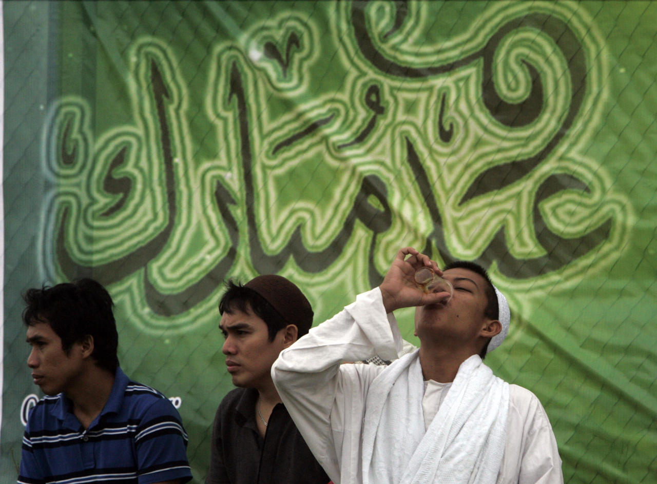 A Filipino Muslim takes a drink after the morning prayer celebrating Eid al-Fitr, a Muslim holiday marking the end of Ramadan, the Islamic holy month of fasting, at the Quirino grandstand in Manila, Philippines, Tuesday, Aug. 30, 2011. (AP Photo/Pat Roque)