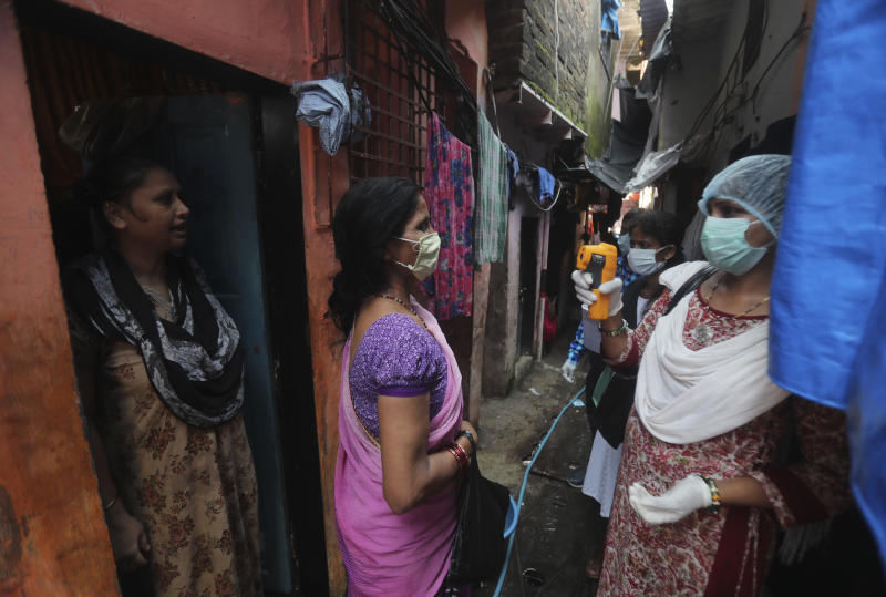 A health worker screens people for symptoms of COVID-19 in Dharavi, one of Asia's biggest slums, in Mumbai, India on Friday. Source: AAP