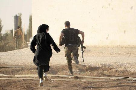A woman reporter runs with a rebel fighter to avoid snipers at the frontline against the Islamic State fighters in Aleppo's northern countryside October 10, 2014. REUTERS/Jalal Al-Mamo