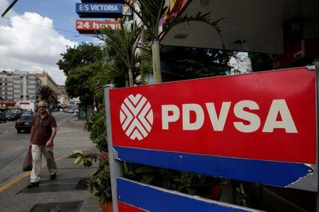 FILE PHOTO: Man walks past PDVSA corporate logo at  gas station in Caracas