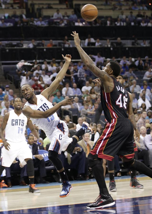 Charlotte Bobcats' Kemba Walker (15) is fouled by Miami Heat's Udonis Haslem (40) during the first half in Game 4 of an opening-round NBA basketball playoff series in Charlotte, N.C., Monday, April 28, 2014. (AP Photo/Chuck Burton)