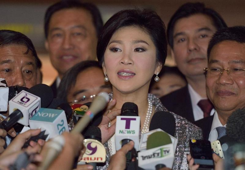 Ousted Thai prime minister Yingluck Shinawatra (C) answers media questions prior to facing impeachment proceedings by the military-stacked National Legislative Assembly, at the parliament in Bangkok, on January 22, 2015 (AFP Photo/Pornchai Kittiwongsakul)