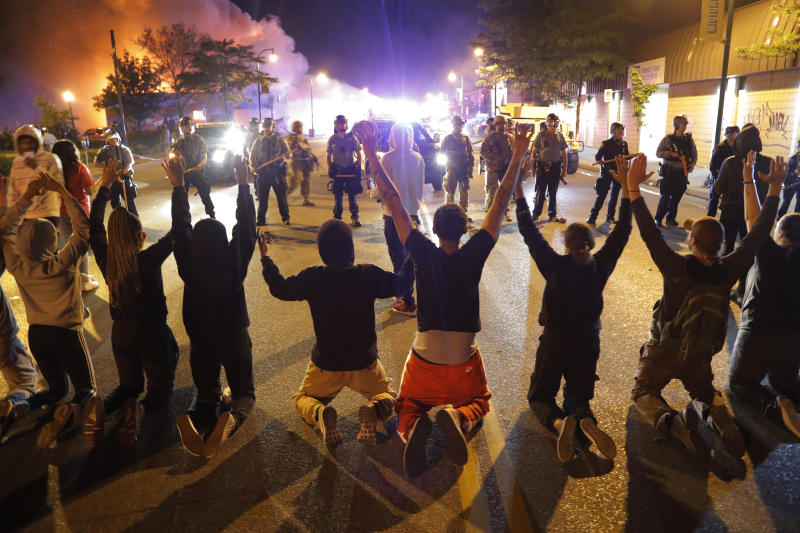Demonstrators kneel before police early Saturday morning in Minneapolis. Source: AP