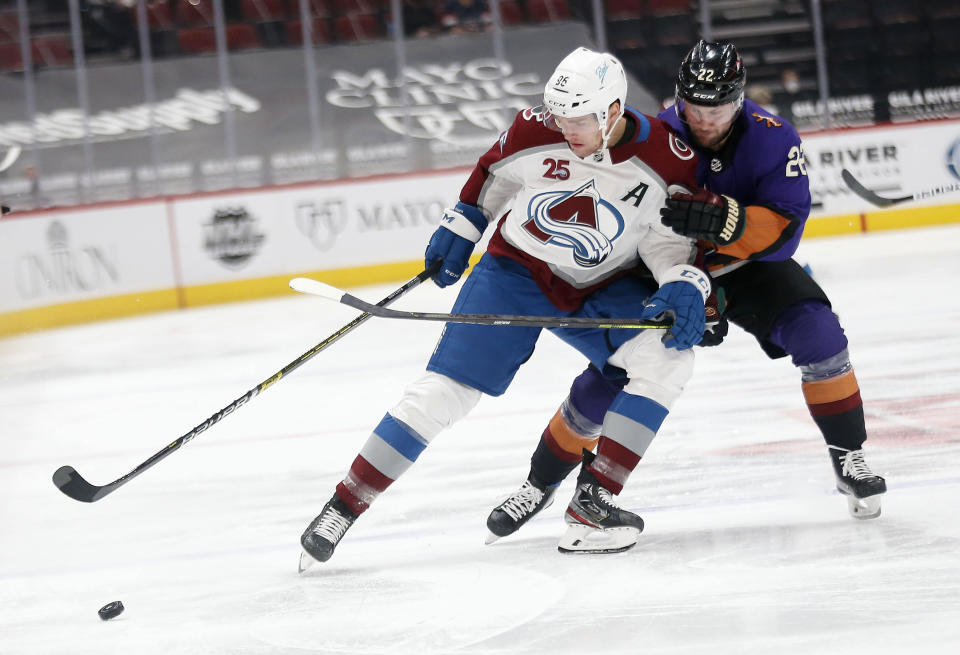 Colorado Avalanche's Logan O'Connor protects the puck from Arizona Coyotes' Johan Larsson during the first period of an NHL hockey game Saturday, Feb. 27, 2021, in Glendale, Ariz. (AP Photo/Darryl Webb)