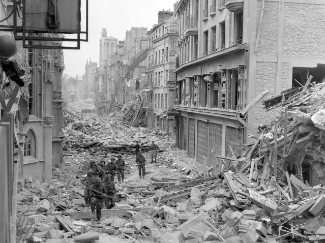 <p>Canadian troops patrol the destroyed Rue Saint-Pierre after German forces were dislodged from Caen, France, in July 1944. (Photo: U.S. National Archives/handout via Reuters) </p>