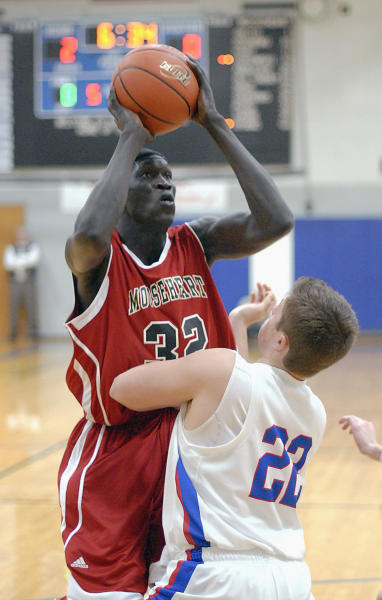 In this Dec. 5, 2012 photo, Mooseheart High School's Makur Puou (32) shoots over Hinckley-Big Rock's Mitch Ruh during a high school basketball game in Hinckley, Ill. Puou is one of four Sudanese athletes who find themselves at center court of a controversy in suburban Chicago over high schools recruiting athletes. The Illinois High School Association board will consider Monday, Dec. 10 whether the three basketball players and a cross-country runner are ineligible to continue competing for Mooseheart. The century-old school says it accepted the students as part of its tradition of helping troubled and poor students, but the ISHA's executive director determined that it broke a prohibition against recruiting athletes after accepting the young men from an Indiana outfit called A-HOPE, an Indiana-based foundation whose founder has drawn NCAA scrutiny. (AP Photo/Daily Herald, Laura Stoecker) MANDATORY CREDIT, MAGS OUT, TV OUT