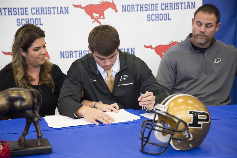 FILE - In this Feb. 1, 2017, file photo, Northside Christian High School quarterback Griffin Alstott gets help from his mom, Nicole, on where to sign as he commits to Purdue University at Northside Christian High School on National Signing Day in St. Petersburg, Fla. At right is his father, Mike Alstott, who used to play for the Tampa Bay Buccaneers. The NCAA has voted to allow high school football players to sign with colleges as early as December, make early official visits and put a two-year waiting period on Bowl Subdivision teams from hiring people close to a recruit. If approved by the Board of Governors on April 26, the signing period change would take effect Aug. 1. (Eve Edelheit/The Tampa Bay Times via AP, File)