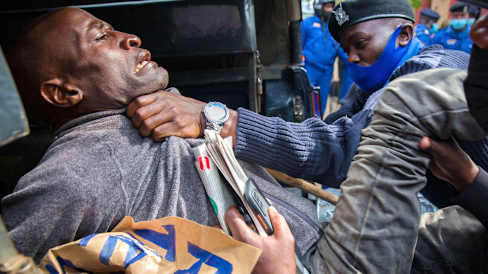 A protester being manhandled by a police officer in Nairobi, Kenya - Saturday 1 May 2021