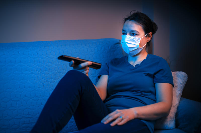 Young Female with medical mask sitting on sofa and look at tv. Concept of persona in quarantine (self-isolation)