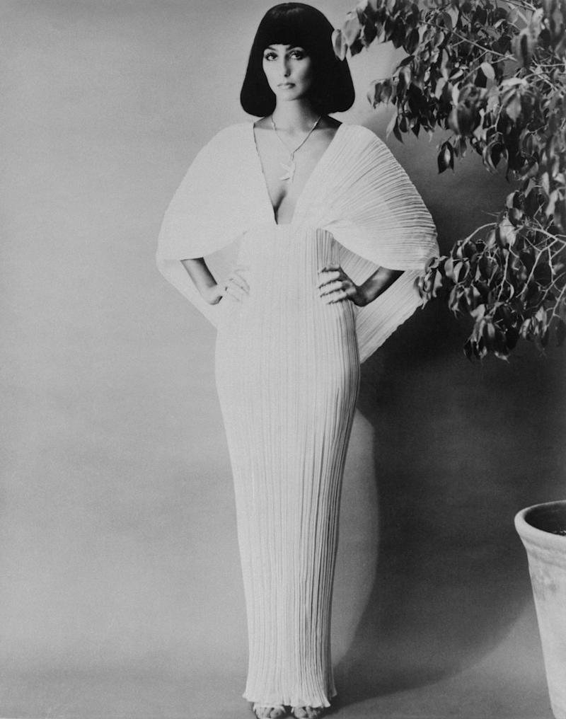 Singer Cher Bono, modeling elegant gowns and outfits. Photo shows Cher modeling white gown with low neck line, both hands on her hips, her hair cut Cleopatra style. She is standing near a large potted plant.