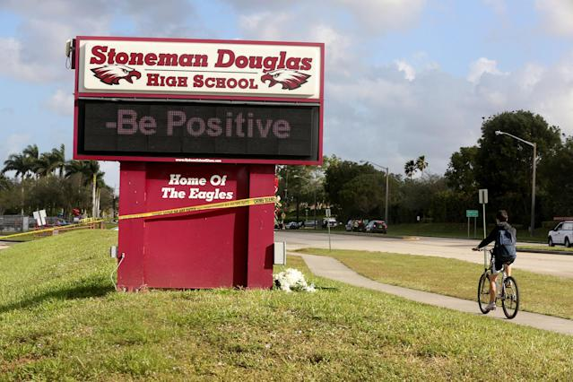<p>A bicyclist rides past a sign at Marjory Stoneman Douglas High School on Friday, Feb. 23, 2018 in Parkland, Fla. Teachers and administrators returned for the first time since the Valentine's Day shooting that killed several people. (Photo: Mike Stocker/South Florida Sun-Sentinel via AP) </p>