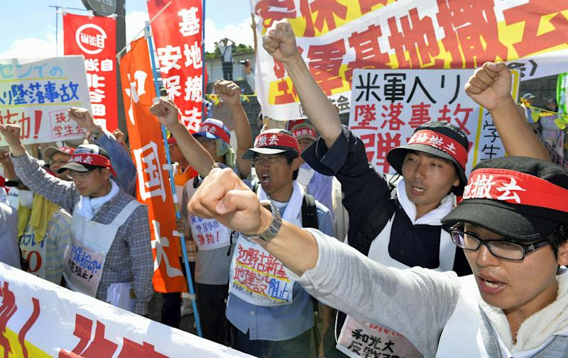 Protesters chant slogans against Monday's accident of a U.S. military helicopter crash and planned additional deployment of Osprey transport aircraft in front of a gate to U.S. Marine Corps Futenma Air Station in Ginowan, Okinawa, southwestern Japan Tuesday, Aug. 6, 2013. Japan has asked the U.S. military not to fly its HH-60 helicopters until it determines what caused one to crash Monday at a U.S. base on the southern island of Okinawa. Defense Minister Itsunori Onodera said Tuesday that he had conveyed the request to the U.S. military. (AP Photo/Kyodo News) JAPAN OUT, MANDATORY CREDIT