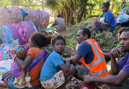 Residents sit with their possessions as they prepare to board a boat at Lolowai Port as they evacuate due to the Manaro Voui volcano continuing to emanate smoke and ash on Vanuatu's northern island of Ambae in the South Pacific, October 1, 2017. Picture taken October 1, 2017.    REUTERS/Ben Bohane