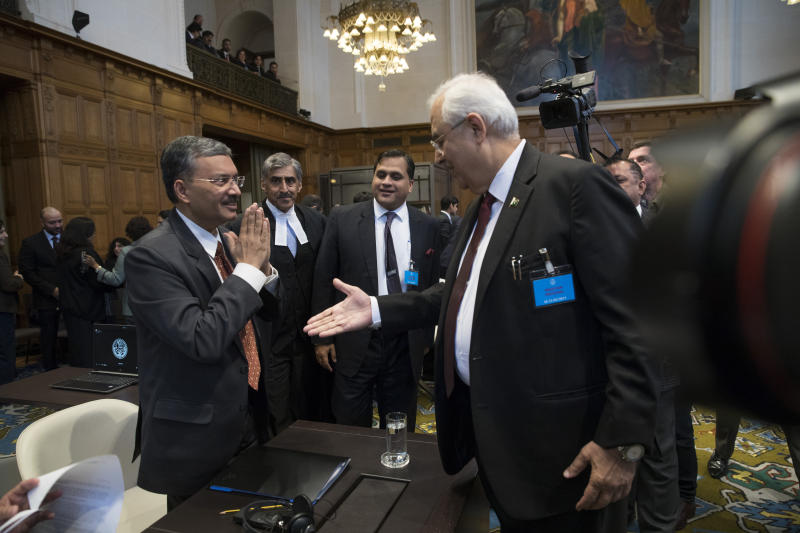 Pakistan's attorney general Anwar Mansoor Khan, right, greets Deepak Mittal, the joint secretary of India's Foreign Ministry, as he present oral arguments at the International Court of Justice, or World Court, in The Hague, Netherlands, Monday, Feb. 18, 2019. India is taking Pakistan to the United Nations' highest court in an attempt to save the life of an Indian naval officer sentenced to death last month by a Pakistani military court after being convicted of espionage.(AP Photo/Peter Dejong)