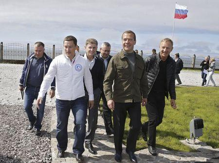 """Russia's Prime Minister Dmitry Medvedev (2nd R, front), accompanied by Minister of Education and Science Dmitry Livanov (R) and other officials, attends the all-Russian youth educational forum """"Iturup"""" in Kurilsk during his visit to Iturup Island, one of four islands known as the Southern Kurils in Russia and the Northern Territories in Japan, August 22, 2015. REUTERS/Dmitry Astakhov/RIA Novosti/Pool"""