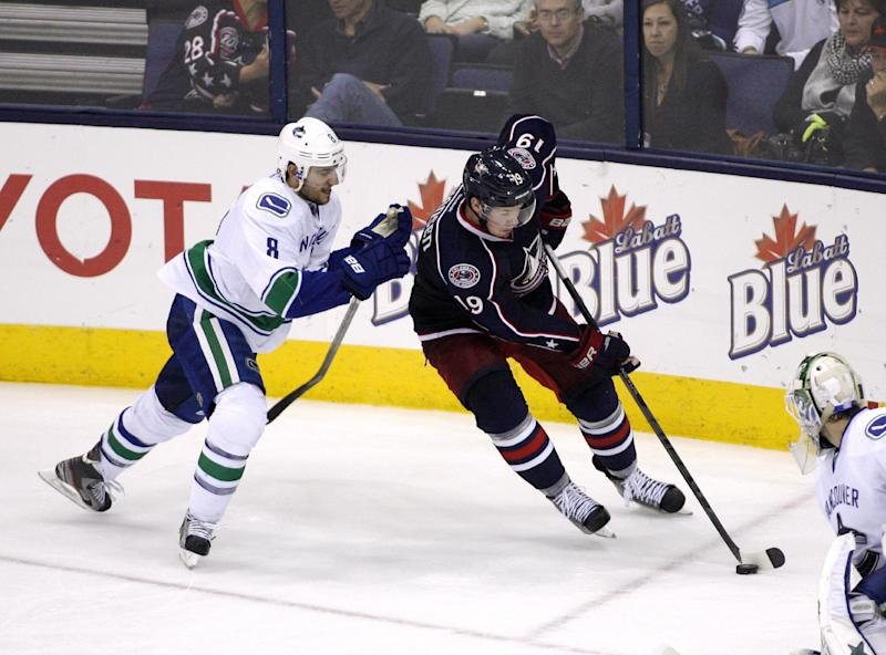 Columbus' Ryan Johansen, right, moves to score as Vancouver's Christopher Tanev closes in during the third period of an NHL hockey game, Sunday Oct. 20, 2013, in Columbus, Ohio. (AP Photo/ Mike Munden)