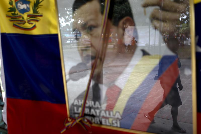 A woman is reflected in a window displaying a poster of the late President Hugo Chavez at a school where he studied in Sabaneta, western Venezuela, Saturday, March 9, 2013. Chavez, who died of cancer on March 5, 2013 was born in Sabaneta. (AP Photo/Esteban Felix)