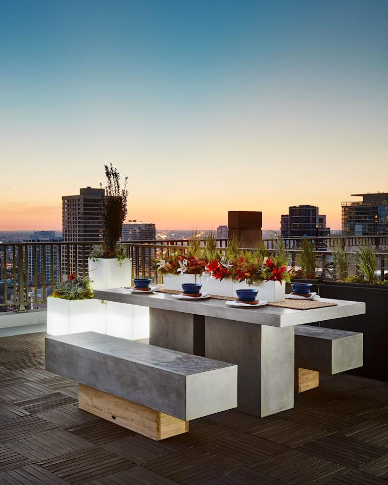 """<p>A Gold Coast private rooftop deck conjures modern picnic vibes, with a stone-and-wood dining table that's backed by sprawling city views.</p><p><em>Design by <a href=""""https://deringhall.com/interior-designers/inspired-interiors"""" target=""""_parent"""">Inspired Interiors</a></em></p>"""