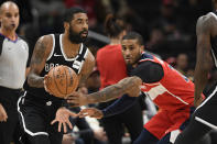 Brooklyn Nets guard Kyrie Irving, front left, dribbles the ball past Washington Wizards guard Gary Payton II, right, during the first half of an NBA basketball game, Saturday, Feb. 1, 2020, in Washington. (AP Photo/Nick Wass)
