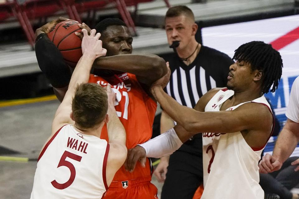 Illinois's Kofi Cockburn gets tied up by Wisconsin's Tyler Wahl and Aleem Ford during the second half of an NCAA college basketball game Saturday, Feb. 27, 2021, in Madison, Wis. (AP Photo/Morry Gash)