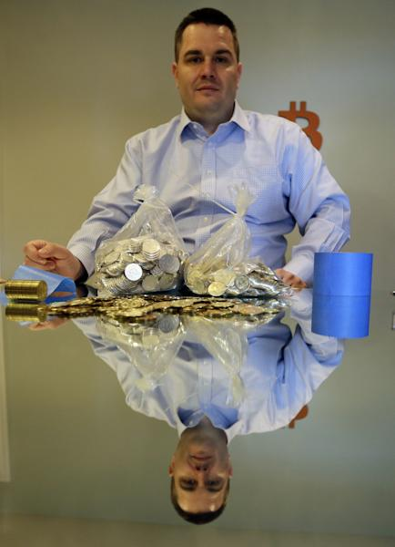 In this April 3, 2013 photo, Mike Caldwell, a 35-year-old software engineer, poses with bitcoin tokens at his shop in Sandy, Utah. Caldwell mints physical versions of bitcoins, cranking out homemade tokens with codes protected by tamper-proof holographic seals, a retro-futuristic kind of prepaid cash. With up to 70,000 transactions each day over the past month, bitcoins have been propelled from the world of Internet oddities to the cusp of mainstream use, a remarkable breakthrough for a currency which made its online debut only four years ago. (AP Photo/Rick Bowmer)