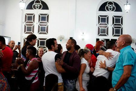 People embrace each other during a mass in a church in Matanzas, Cuba, May 5, 2017. Picture taken on May 5, 2017. REUTERS/Alexandre Meneghini