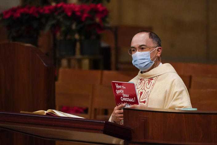 """Father David Gallardo holds up a copy of Dr. Seuss' """"How the Grinch Stole Christmas"""" and likens the Grinch to COVID-10 during a Christmas Eve Mass at Cathedral of Our Lady of the Angels Thursday, Dec 24, 2020, in Los Angeles. California became the first state to record 2 million confirmed coronavirus cases, reaching the milestone on Christmas Eve as nearly the entire state was under a strict stay-at-home order and hospitals were flooded with the largest crush of cases since the pandemic began. (AP Photo/Ashley Landis)"""