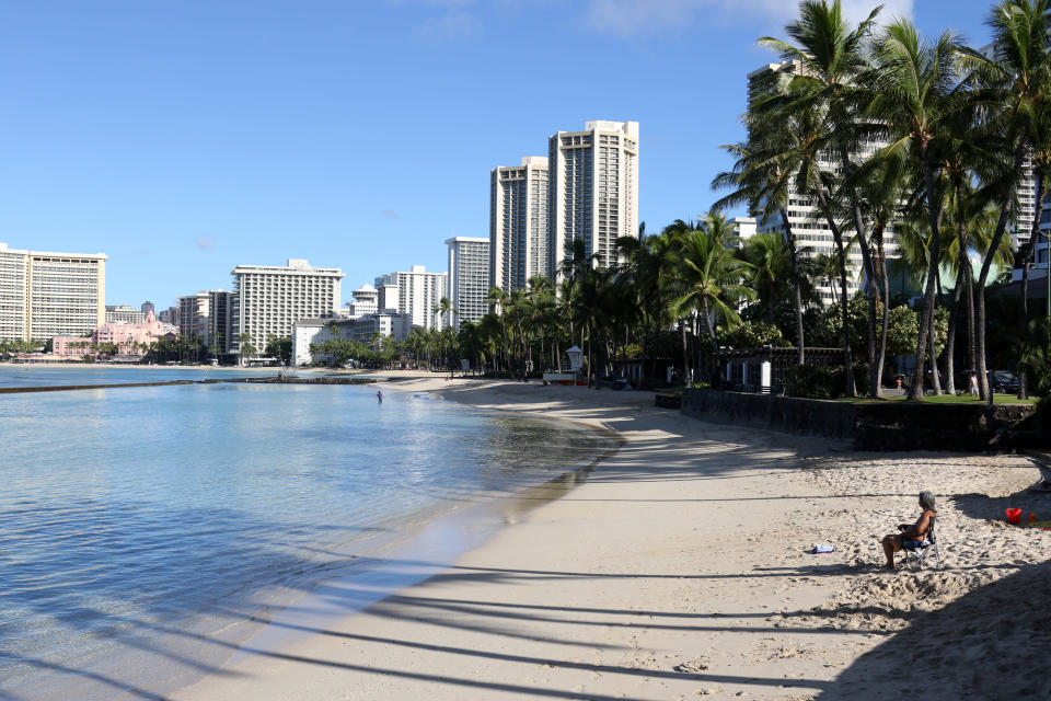 A man sits on a nearly empty Waikiki Beach in Honolulu, Friday, Oct. 2, 2020. After a summer marked by a surge of coronavirus cases in Hawaii, officials plan to reboot the tourism based economy later this month despite concerns about the state's pre-travel testing program. (AP Photo/Caleb Jones)