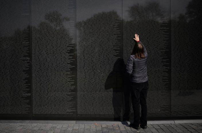 A woman places her hand on the Vietnam War Memorial on Veterans Day on Nov. 11, 2019 in Washington, DC. (Photo: Mandel Ngan/AFP via Getty Images)
