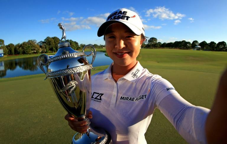 Soggy from champagne, Kim Sei-young holds the trophy after winning the Pelican Women's Championship in Belleair, Florida