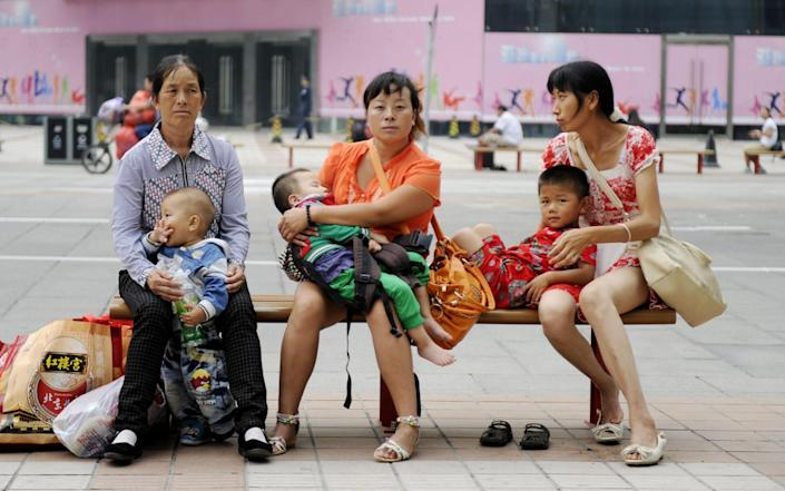Chinese women with their babies as they sit on a bench along a street in Beijing - AFP