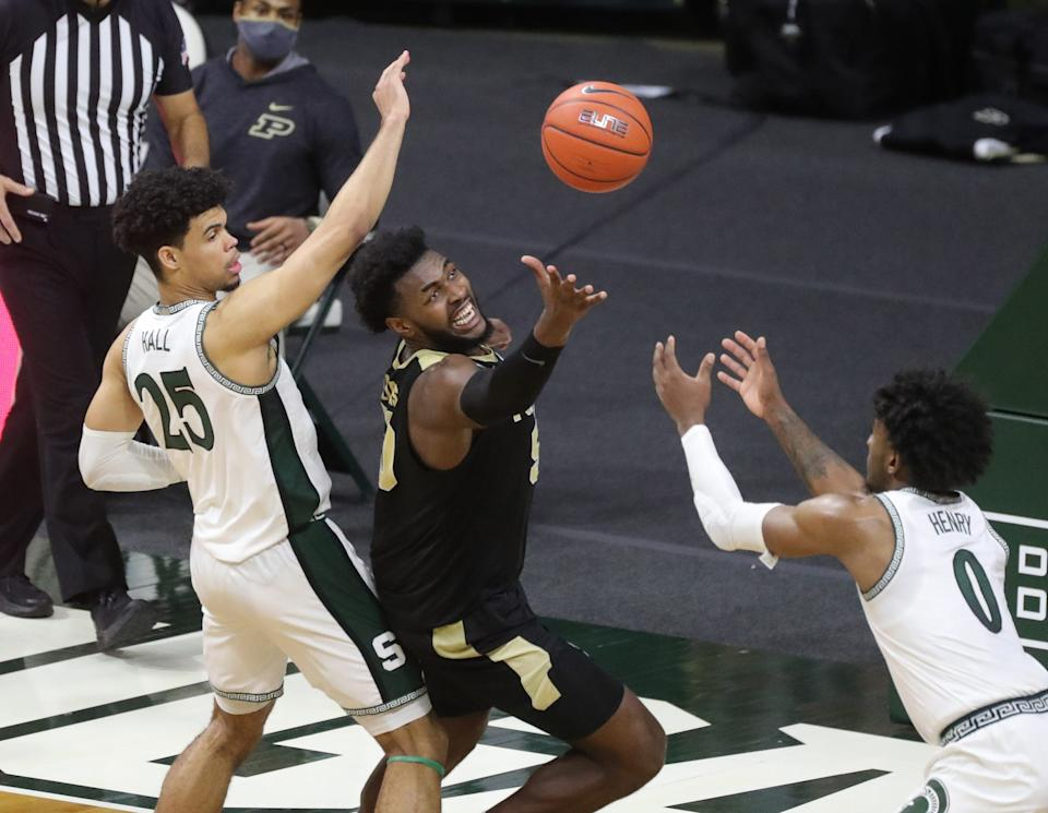 Michigan State Spartans forwards Malik Hall (25) and Aaron Henry defend Purdue Boilermakers forward Trevion Williams during the second half at Breslin Center in East Lansing, Friday, Jan. 8, 2021.