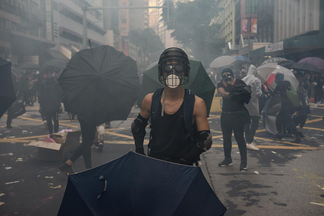 A protester holds an umbrella surrounded by tear gas as thousands of anti-China protesters clash with police in Hong Kong on October 01, 2019. | Miguel Candela Poblacion/Anadolu Agency via Getty Images
