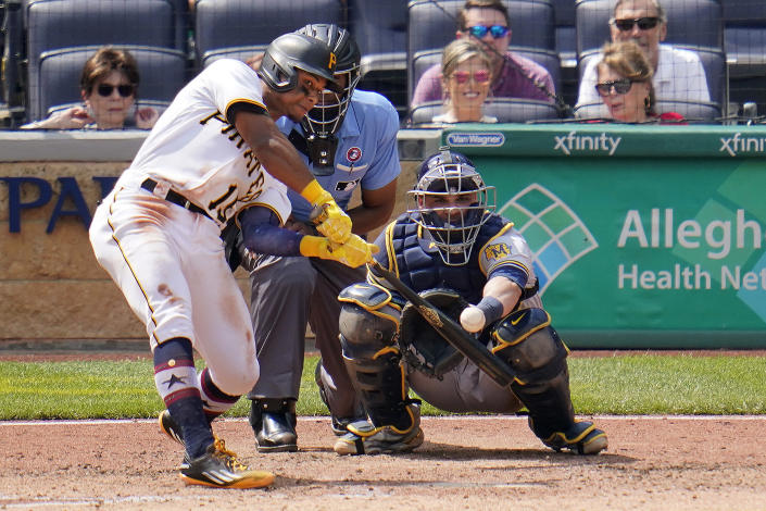 Pittsburgh Pirates Wilmer Difo, left, doubles off Milwaukee Brewers relief pitcher Freddy Peralta, driving in a run, during the sixth inning of a baseball game in Pittsburgh, Sunday, July 4, 2021 Brewers catcher Manny Pina, right, looks on. (AP Photo/Gene J. Puskar)