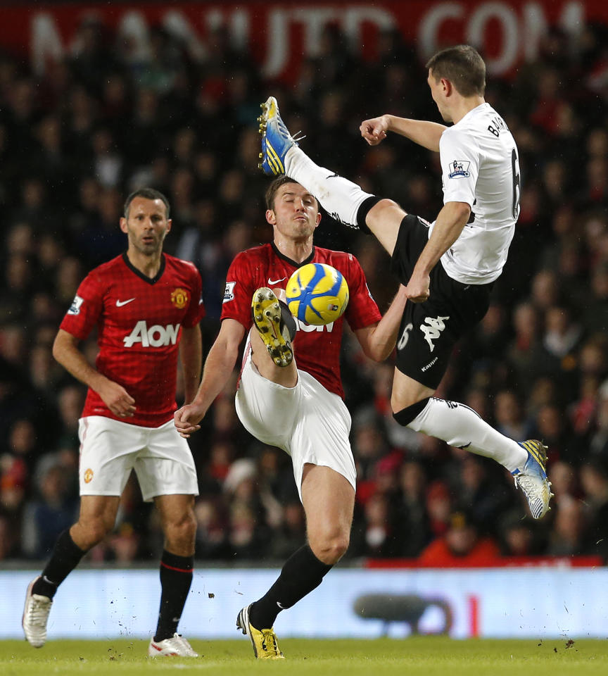 Manchester United's Michael Carrick (C) is challenged by Fulham's Chris Baird (R) during their FA Cup fourth round soccer match at Old Trafford in Manchester, northern England, January 26, 2013. REUTERS/Phil Noble (BRITAIN - Tags: SPORT SOCCER TPX IMAGES OF THE DAY) - RTR3D00L