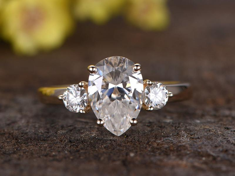 """<i><a href=""""https://www.bbbgem.com/2-2-carat-pear-moissanite-engagement-ring-promise-14k-yellow-gold-three-stone-stacking-band/"""" target=""""_blank"""">Buy it fromBBBGEM</a> for$1,125.</i>"""