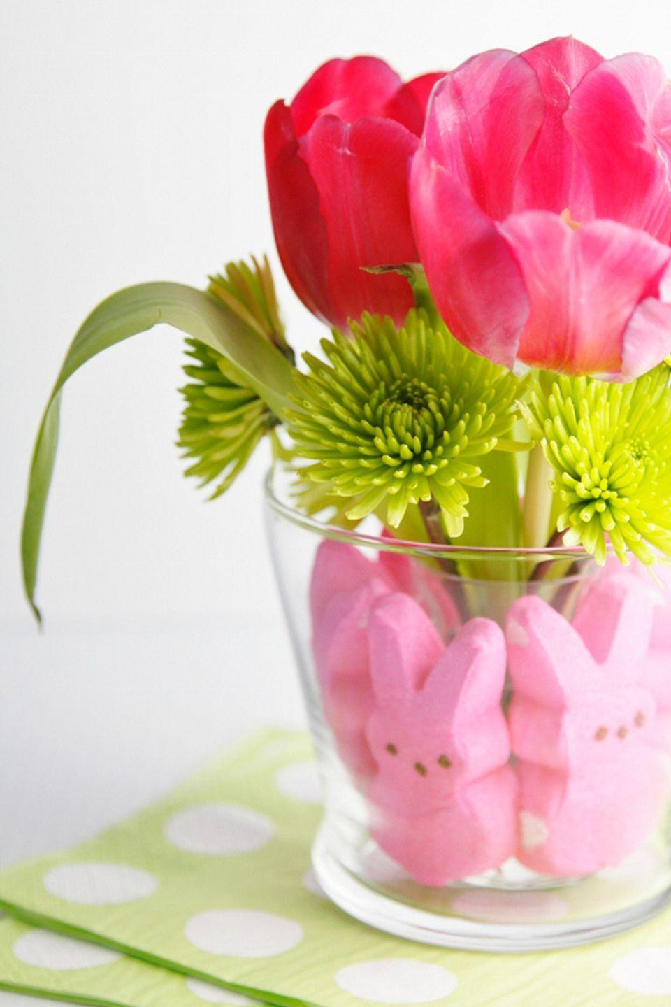 """<p>The key to this arrangement is picking out flowers that are just as vibrant and eye-catching as the pink marshmallow treats around the edge of the vase.</p><p><em><a href=""""https://bellalimento.com/2013/02/19/diy-peeps-centerpiece/"""" rel=""""nofollow noopener"""" target=""""_blank"""" data-ylk=""""slk:Get the tutorial at Bell'alimento »"""" class=""""link rapid-noclick-resp"""">Get the tutorial at Bell'alimento »</a></em> </p><p><strong><em>Pottery Barn Shouldered Clear Glass Vase, $41 </em></strong><a class=""""link rapid-noclick-resp"""" href=""""https://go.redirectingat.com?id=74968X1596630&url=https%3A%2F%2Fwww.potterybarn.com%2Fproducts%2Fshouldered-clear-glass-vase%2F&sref=https%3A%2F%2Fwww.housebeautiful.com%2Fentertaining%2Fflower-arrangements%2Fg19409803%2Feaster-flower-arrangements%2F"""" rel=""""nofollow noopener"""" target=""""_blank"""" data-ylk=""""slk:BUY NOW"""">BUY NOW</a></p>"""