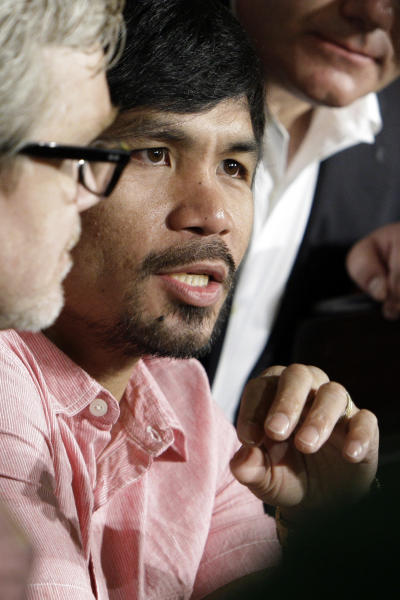 Manny Pacquiao, of the Philippines, right, and his trainer Freddie Roach talk with reporters at a news conference to promote his upcoming boxing match against Juan Manuel Marquez in Beverly Hills, Calif., Monday, Sept. 17, 2012. The two will fight for the fourth time on Dec. 8 in Las Vegas. (AP Photo/Reed Saxon)