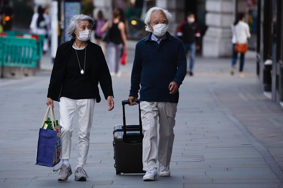 An elderly couple wearing face masks walk along Regent Street in London, England, on September 22, 2020. British Prime Minister Boris Johnson this afternoon announced a raft of new coronavirus restrictions to apply across England, possibly to last the next six months, including requiring pubs and restaurants to close at 10pm and for retail staff to all wear face masks. A return to home working where possible is also being encouraged. The new measures come amid fears of a 'second wave' of covid-19 deaths prompted by rising numbers of people testing positive in recent weeks. (Photo by David Cliff/NurPhoto via Getty Images)