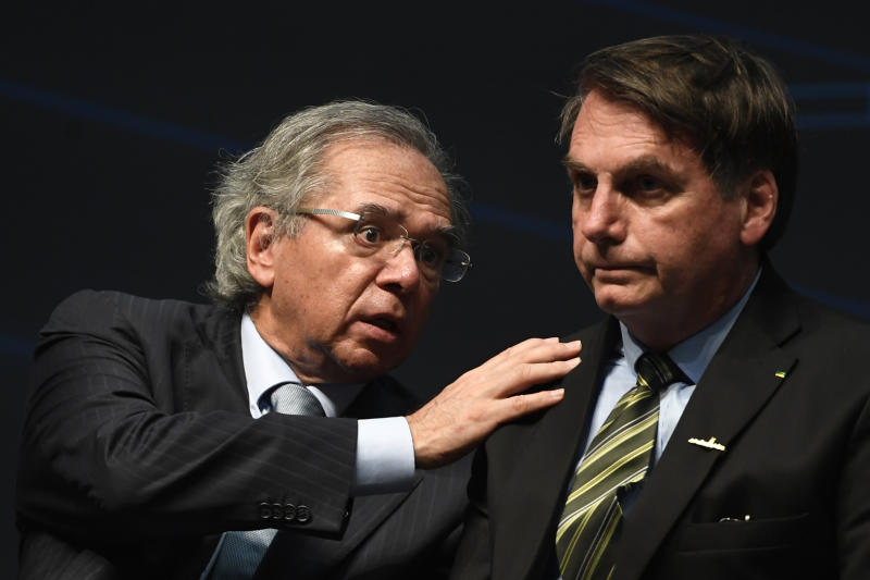 Brazil's Economy Minister Paulo Guedes (L) speaks with Brazilian President Jair Bolsonaro during the ceremony marking the assembly of the parts of Brazil's new Navy submarine Humaita (SBR-2), at the Itaguai Navy Complex in Rio de Janeiro, Brazil, on October 11, 2019. (Photo by MAURO PIMENTEL / AFP) (Photo by MAURO PIMENTEL/AFP via Getty Images)