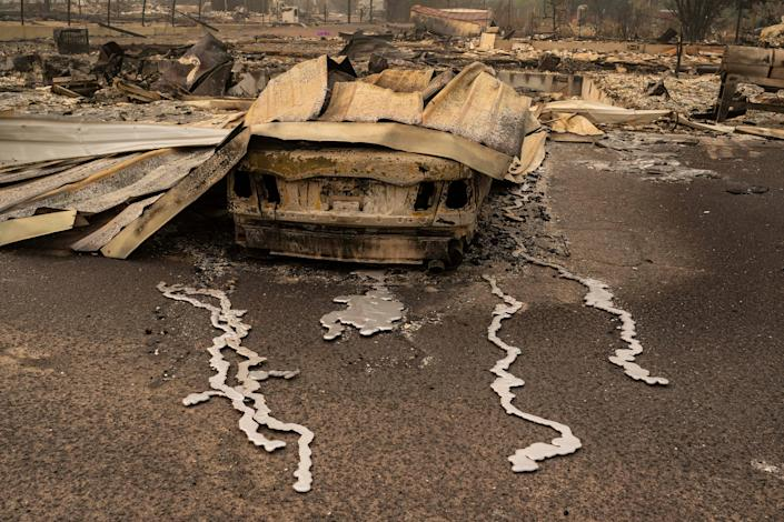 A burnt car sits in a neighborhood destroyed by wildfire on September 13, 2020 in Talent, Oregon.