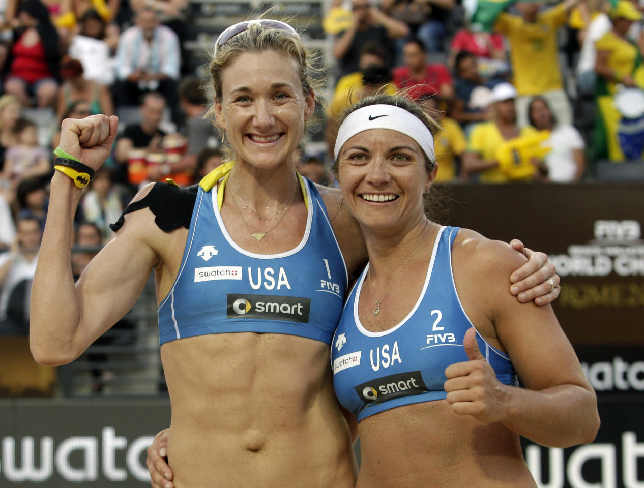FILE - In this June 18, 2011, file photo, U.S. team Misty May-Treanor, left, and Kerri Walsh celebrate after winning the women's beach volleyball World Championships semifinal match against China in Rome. A year and a fortnight before the opening ceremonies, American beach volleyball players are still waiting for the U.S. and international governing bodies to agree on a system to decide who goes to London. (AP Photo/Pier Paolo Cito, File)