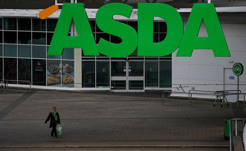 FILE PHOTO: An ASDA employee walks beneath a company logo outside a store in Manchester, northern England.