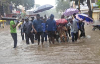A man wearing an oxygen mask is helped on a wheelchair through floodwaters in Kolhapur, in the western Indian state of Maharashtra, Friday, July 23, 2021. Landslides triggered by heavy monsoon rains hit parts of western India, killing more than 30 people and leading to the overnight rescue of more than 1,000 other people trapped by floodwaters, officials said Friday. (AP Photo)