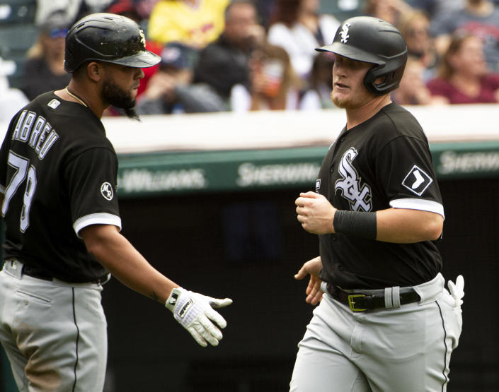 Chicago White Sox's Jose Abreu greets Andrew Vaughn after Vaughn scored on a single by Leury Garcia during the sixth inning of a baseball game in Cleveland, Sunday, Sept. 26, 2021. (AP Photo/Phil Long)