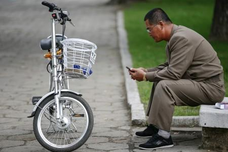 FILE PHOTO : A man uses his mobile phone next to an electric bicycle in downtown Pyongyang