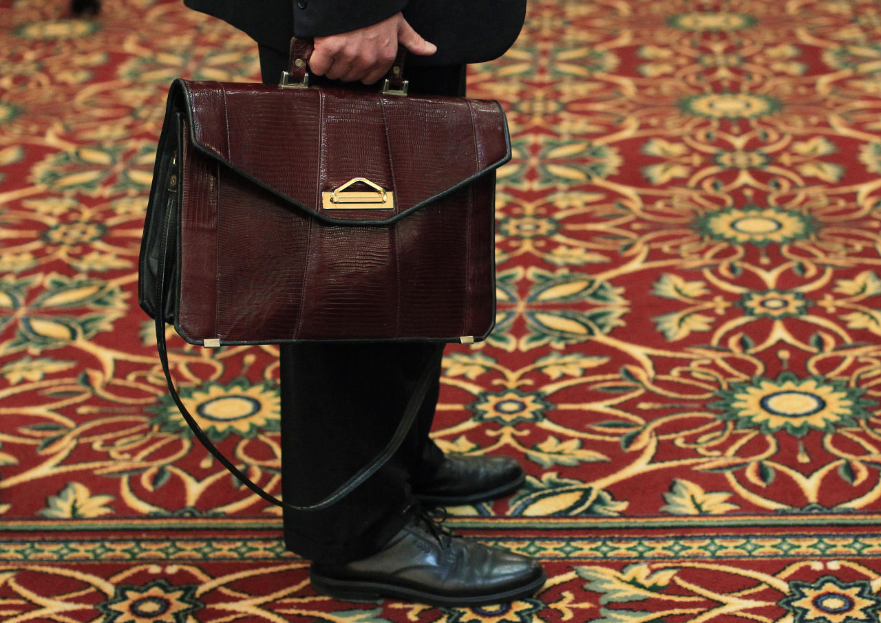 A man holds his briefcase while waiting in line during a job fair in Melville, New York July 19, 2012.  The number of Americans filing new claims for unemployment benefits rebounded last week, returning to levels consistent with only modest job growth after a seasonal quirk caused a sharp drop the prior period. 