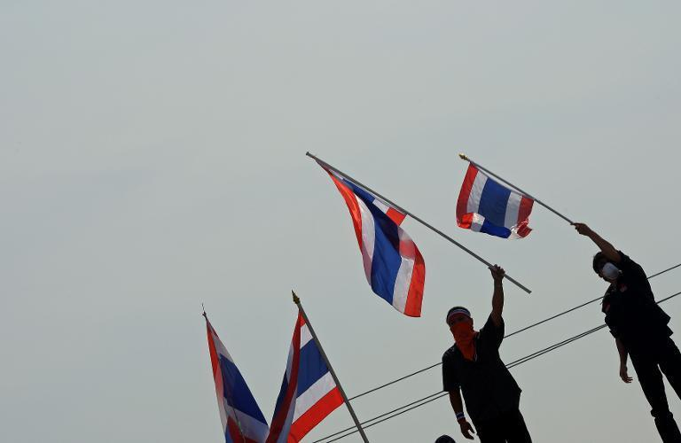 Thai anti-government protesters wave national flags after removing concrete barricades at the Government House in Bangkok, on December 3, 2013