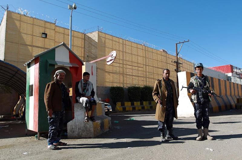 Yemeni security forces stand guard outside the Italian embassy in Sanaa as it was closed temporarily on February 13, 2015 (AFP Photo/Mohammed Huwais)