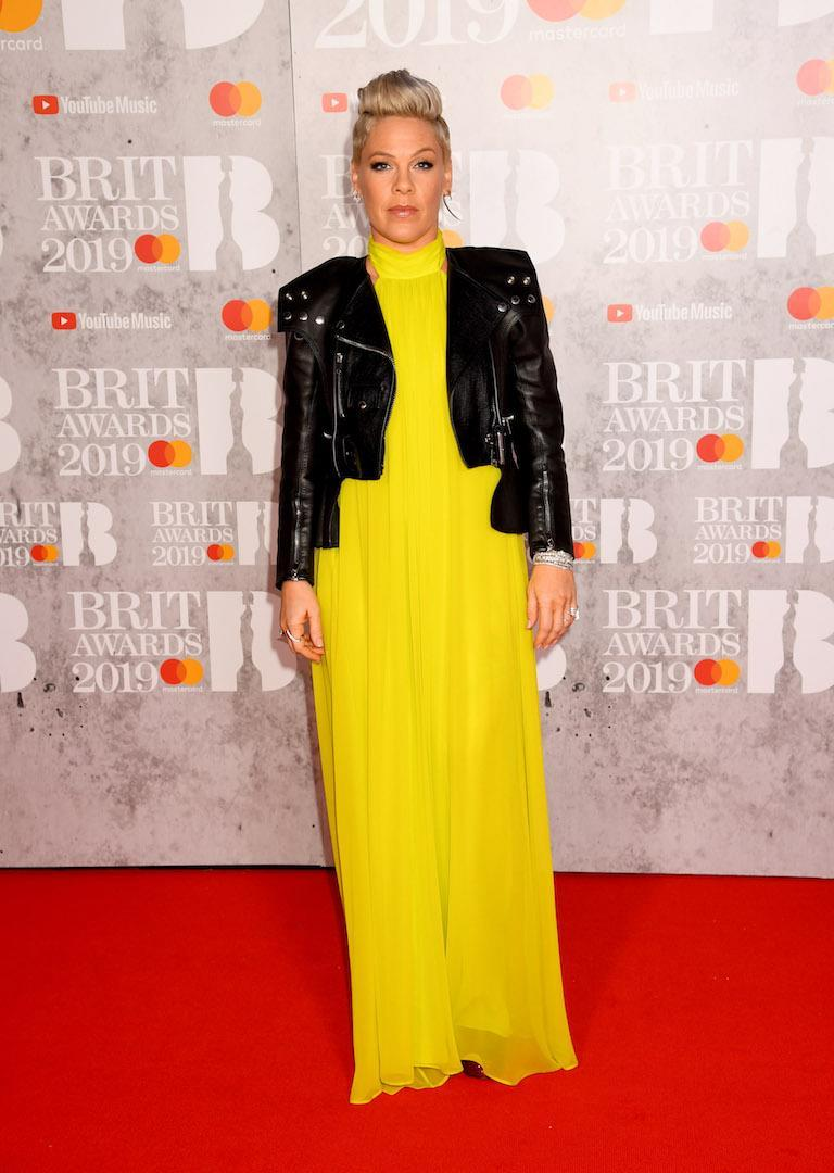 <p>Wearing a neon yellow dress and leather jacket. <em>[Photo: Getty]</em> </p>